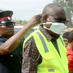 Local Government Minister Charles Banda being helped to put on a mask by his Aide during a cleaning exercise at Lusaka's Chainda Market – Picture By Tenson Mkhala
