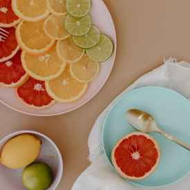 plates with sliced citrus fruits with cutlery near bowl