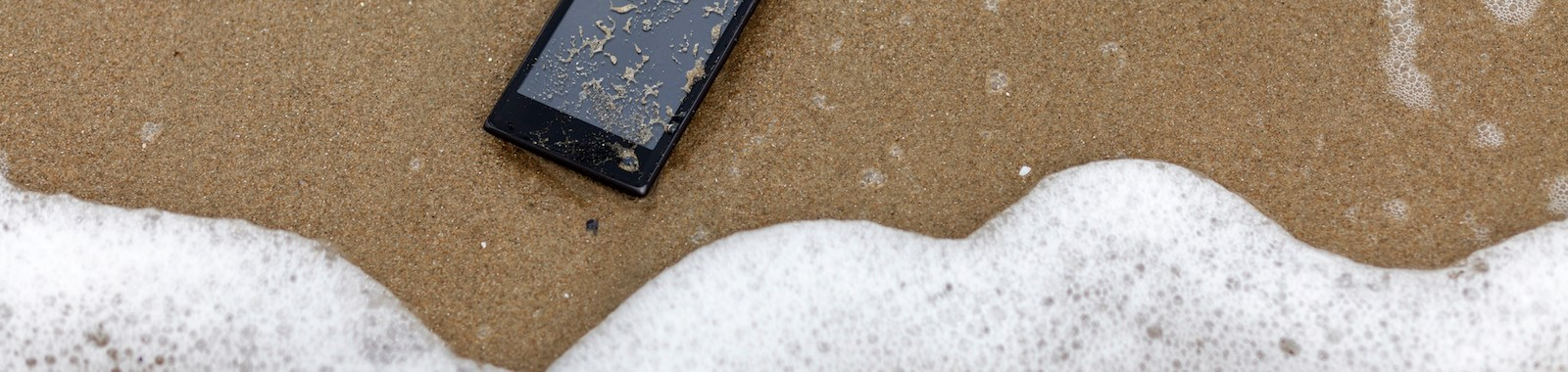 Mobile phone fallen and lost in the sea,  thrown out by a sea wave on the beach