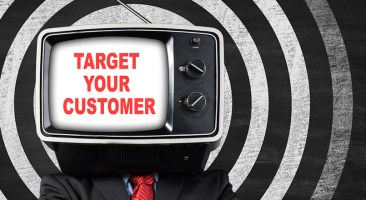 Target Your Customers Businessman with TV head in front of blackboard,