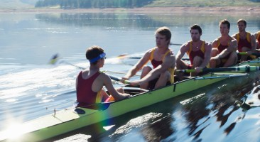 Rowing team rowing scull on lake