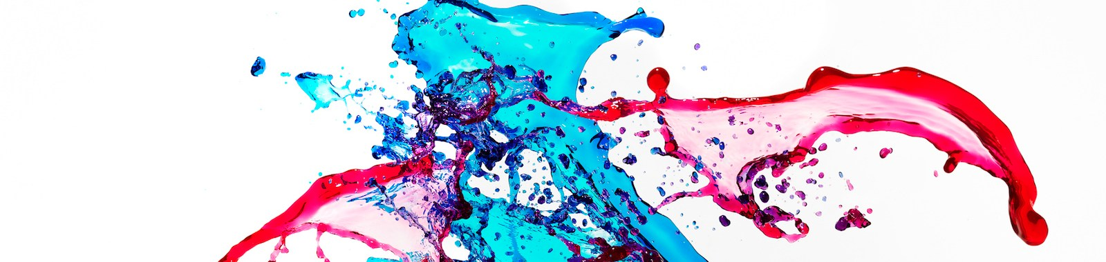 Red and blue colored liquids splashing and mixing on white background