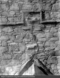 Historic photograph of the East facade of the tower, showing two carved panels: the two fishermen in a boat and, below that, a horse. Source: RCAMS.