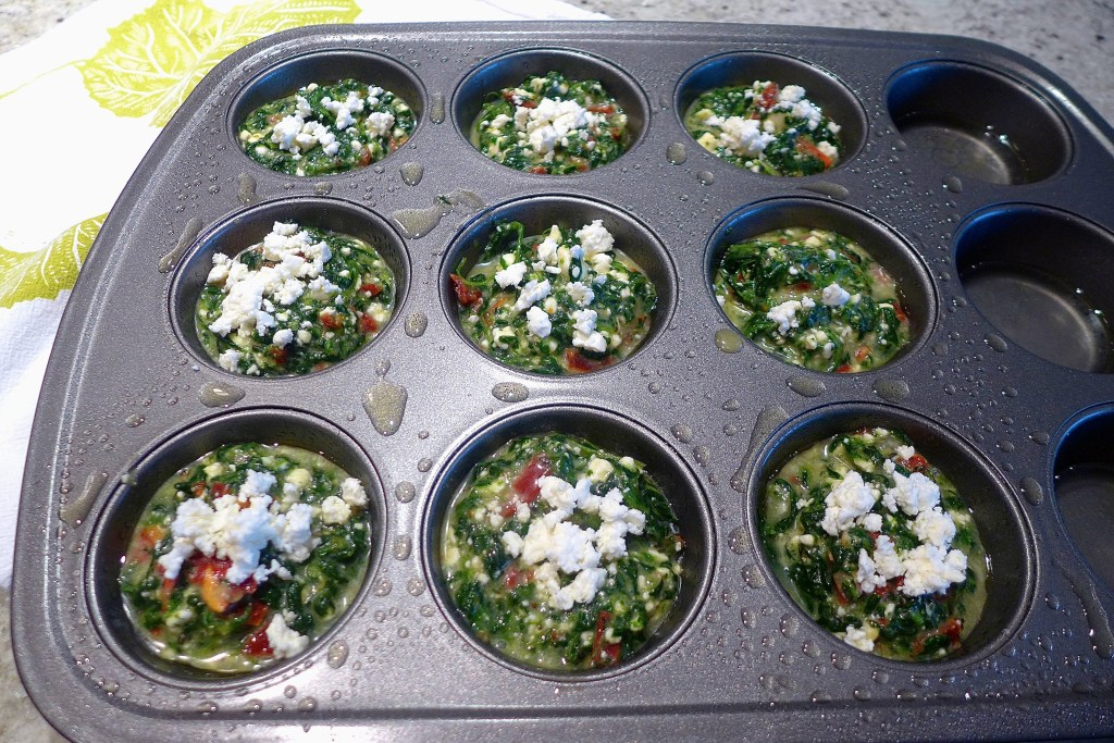 Use a 1/4 cup measure to fill muffin tins. You'll have between 9 - 12 muffins. Top each muffin with a teaspoon of extra feta. Add a little water to empty holes to prevent scorching.