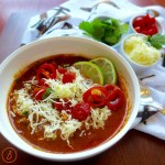 Slow cooked chicken chili with garnishes: cilantro. sliced cherry tomatoes and pepper jack cheddar cheese.