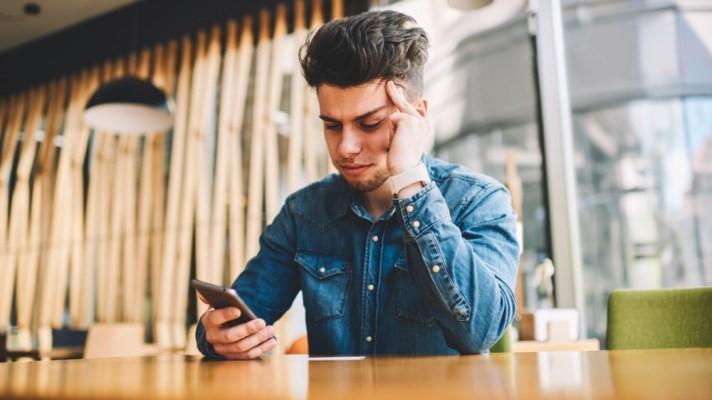 man looking upset using smartphone