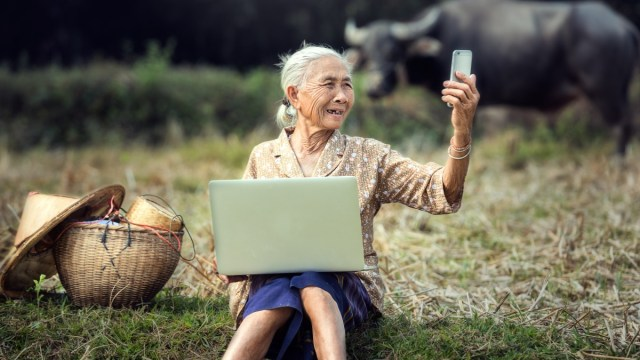 elderly woman with smartphone and laptop