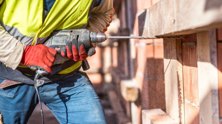 worker using power tools outside in construction
