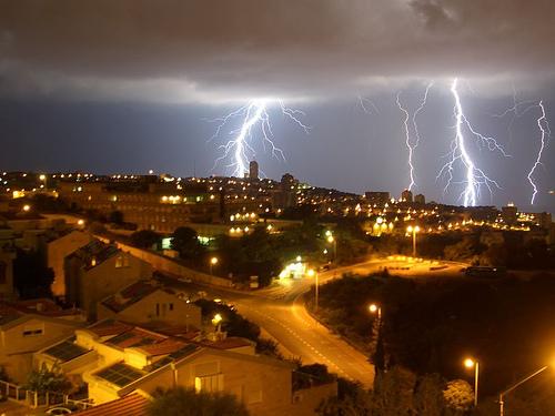 市街地の単色の夜景と垂れこめる雷雲