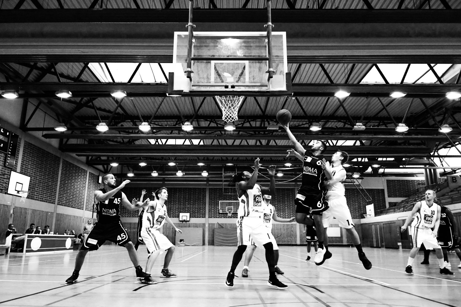 players playing basketball in black and white
