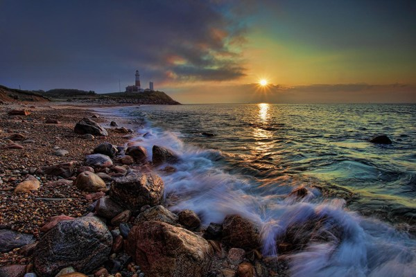 Image: The shoreline in this image leads the viewer's eye right to the lighthouse. The lighthou...