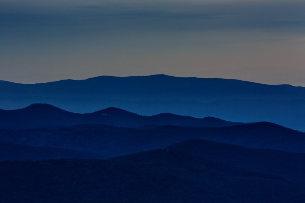"""This shot of the Blue Ridge Mountains was taken with an EOS 5D Mark III and EF 70-200 f/2.8L IS II lens at 200mm. The telephoto nature of the lens compresses the distance between the ridges, creating a flat, graphic look with shades of blue created by the mountains and mist in the valleys. Exposure is 1/3"""", f/16, ISO 400."""