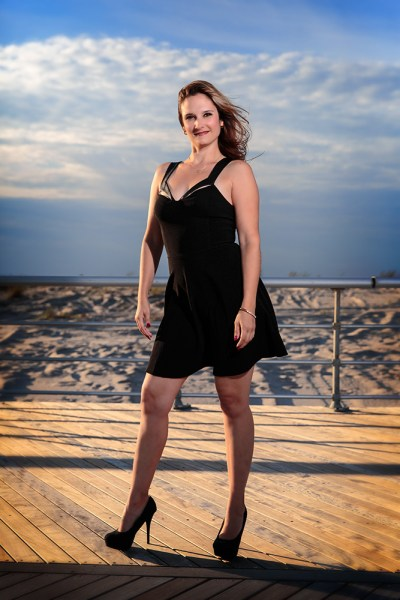 This was one of the first shots taken, on the boardwalk at the beach.  The sun was harsher than I wanted so opted to use wireless flash.  I positioned my friend with the sun at her back and over her right shoulder, and the flash to her front left.  I also had the flash set to high speed sync. I then set the flash to E-TTL, with flash exposure compensation set to even.  I set the camera's exposure compensation to -1, in Aperture Priority.  Doing this lessens the sun's impact on the image, helps darken the sky, and the background overall. Exposure was ISO 100, f/4, 1/4000.