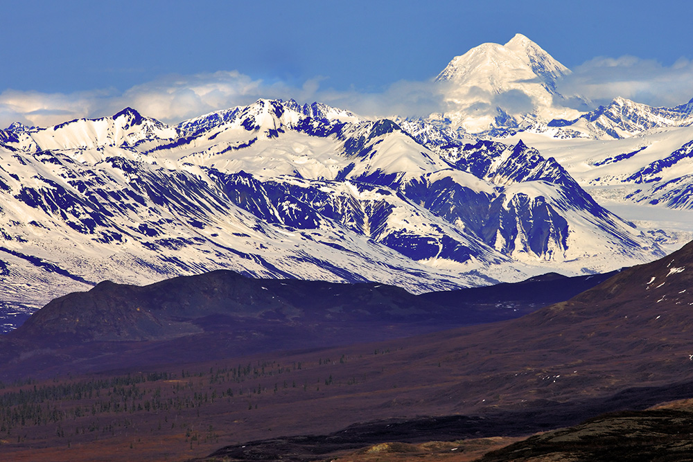 This shot of the Alaska Range was taken from Denali Highway using an EOS-1Ds Mark III and EF 70-200 f/2.8L IS II. The telephoto lens compresses the distance between the foothills and the mountains, making them appear to be right next to each other.