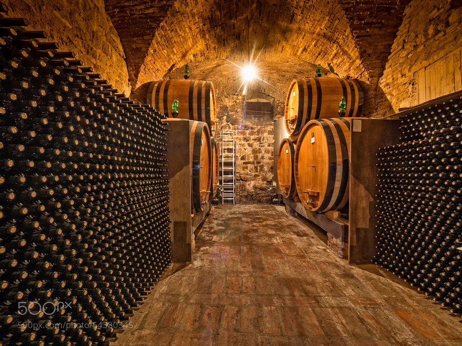 Photograph wine bottles and oak barrels in background by Christian Delbert on 500px