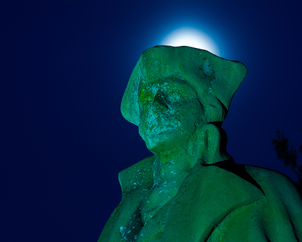 In this image shot at night the white balance was changed to Tungsten, which causes the monument to have a teal color. The glow above the head was created by the moon glow.
