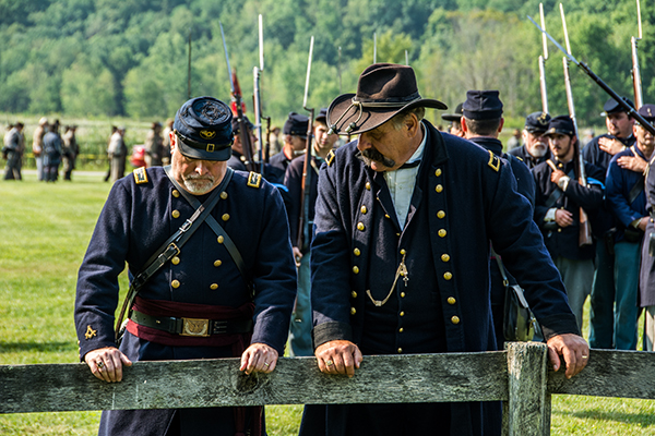 Two officers standing at the fence discussing battle strategy.