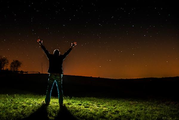pessoa com os braços levantados para o céu