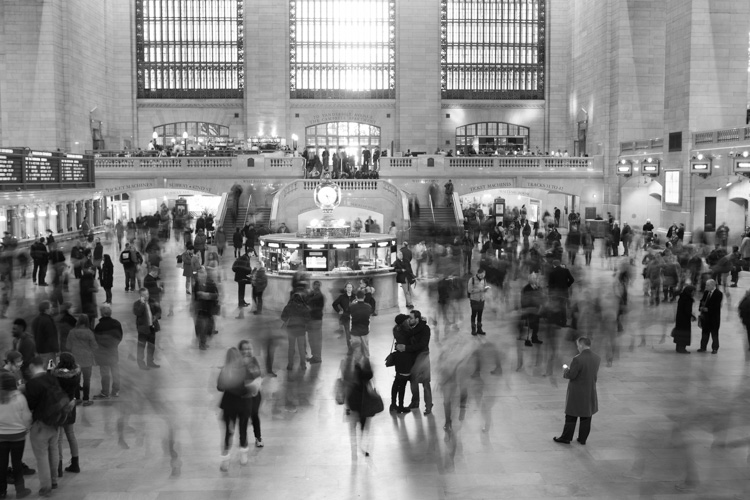 Image: A portrait for an engaged couple in Grand Central Station NYC (seen kissing in foreground)