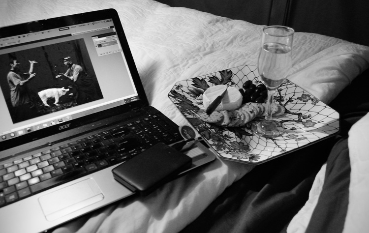 laptop and food on a bed