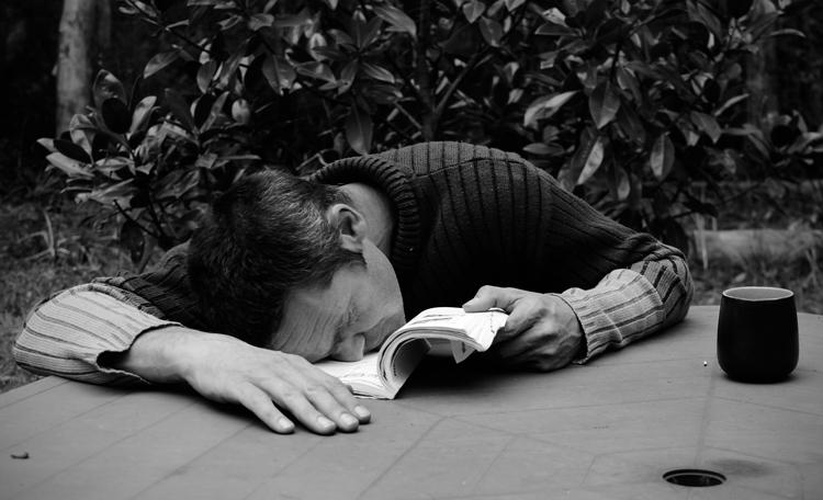 man reading a camera manual falling asleep