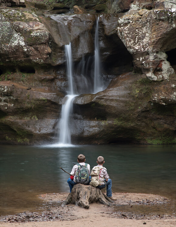Choosing a smaller aperture of f/22 gave enough depth of field to keep both the boys and the waterfalls in focus.