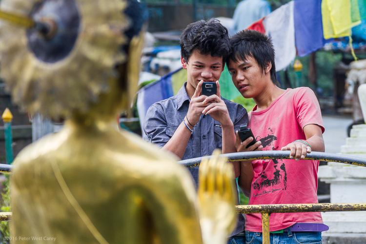 Boys photographing statue of buddha - Nepal