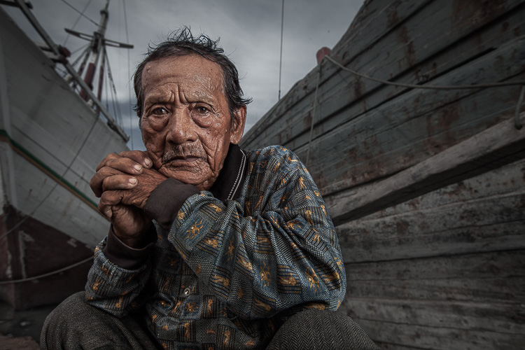 man crouching by ships