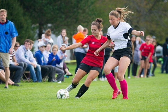 Two soccer players fighting for the ball with spectators watching the game behind them