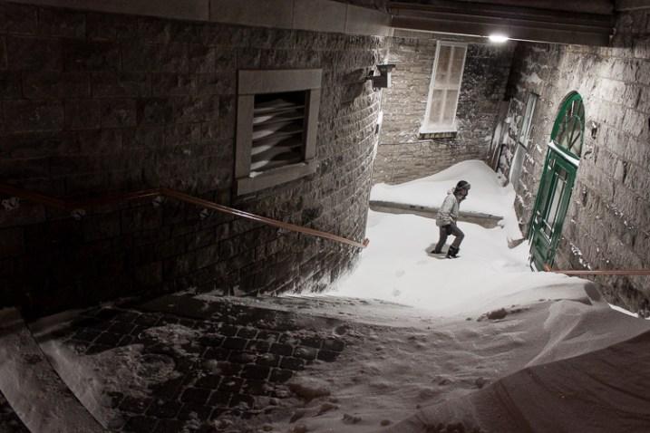 A man explores a snowy entranceway, with sharp textures giving the photo a mood