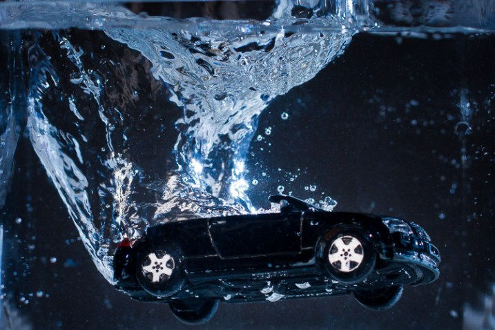 A toy car splashing into water, photography with off-camera flash