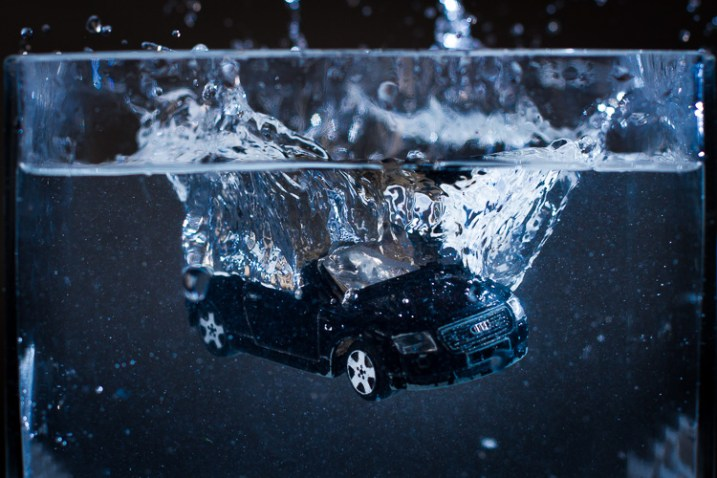 A toy car dropped into water, photographed with off-camera flash