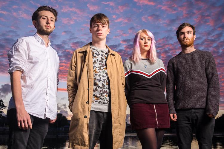 quatro jovens adultos ao pôr do sol