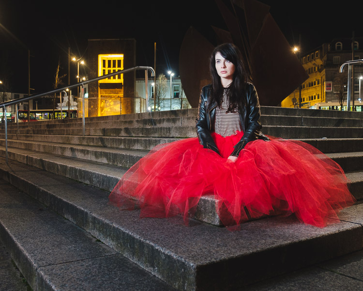 woman in a red skirt at night