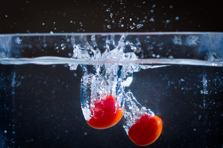 Two tomatoes splashing into water, shot with off-camera flash
