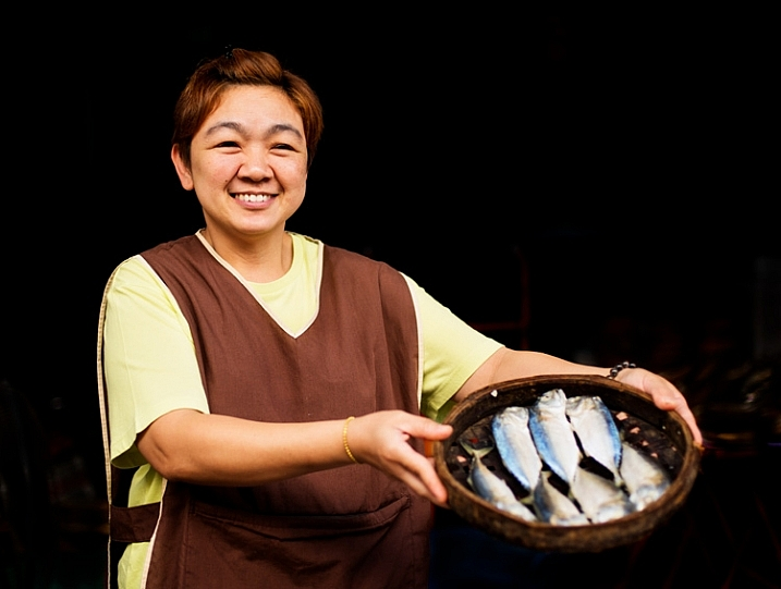 Thai woman holding a bamboo tray of steamed fish - How to Use a Reflector to Improve Your Natural Light Portraits