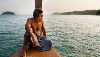 Sea gypsy sitting on the bow of his boat