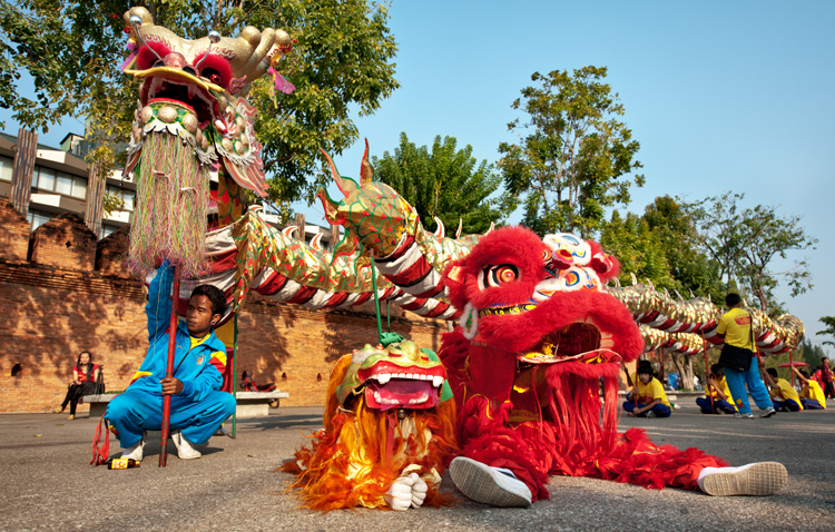 Performers rest prior to the start of a Chinese New Year parade in Chiang Mai, Thailand