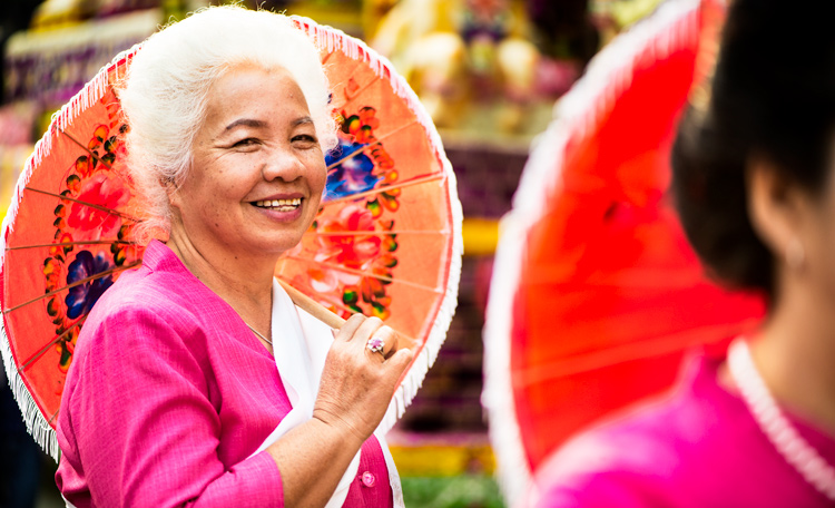 senior Thai woman taking part in a street parade holding a painted parasol - How to be Better Prepared for Your Next Photo Shoot