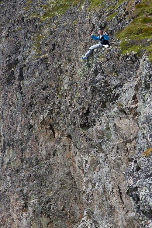 一个男人坐在山边的岩石上-如何在摄影中表现出规模感