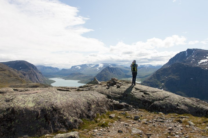 A man taking a photograph in a mountain range - How to Show a Sense of Scale in Your Photography