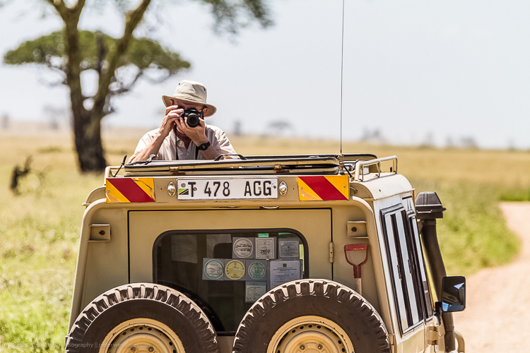 Tips for Making Your Travel Photography Packing List for International Trips - guy taking a photo on a safari
