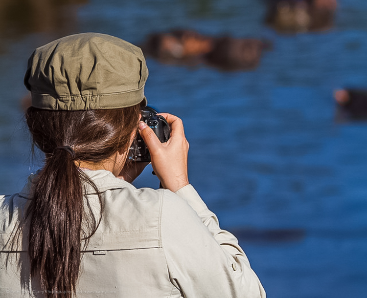 girl taking a photo of a lake - Tips for Making Your Travel Photography Packing List for International Trips
