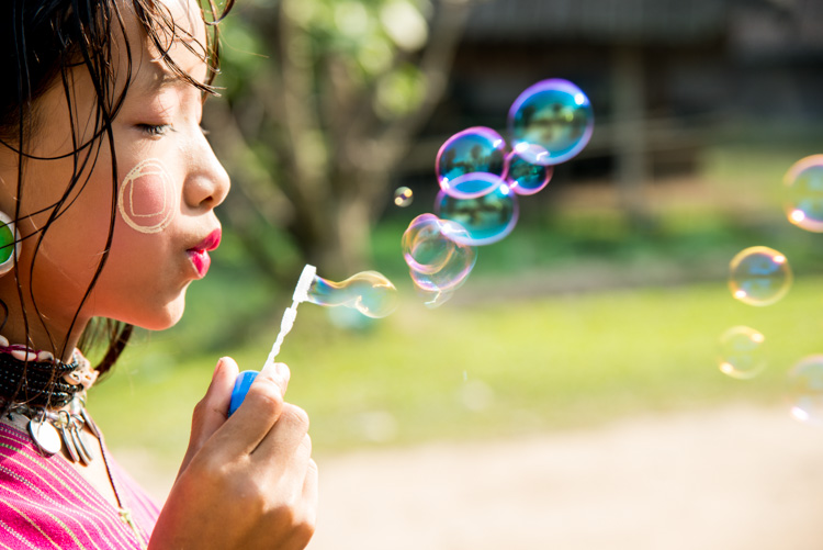 Kayaw girl blowing bubbles in Chiang Mai, Thailand.