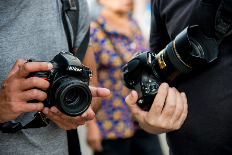 Close up of twp people holding DSLR cameras - ISO settings