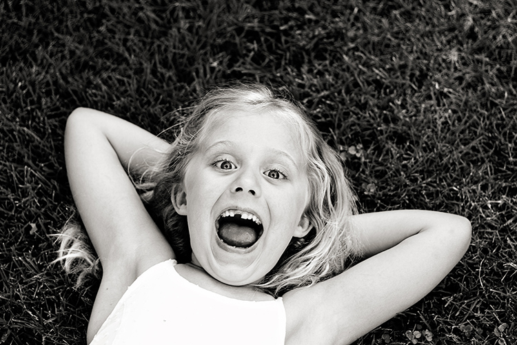 How to do Gentle Posing: A Collection of Prompts to Get You Started - young girl grinning with missing tooth