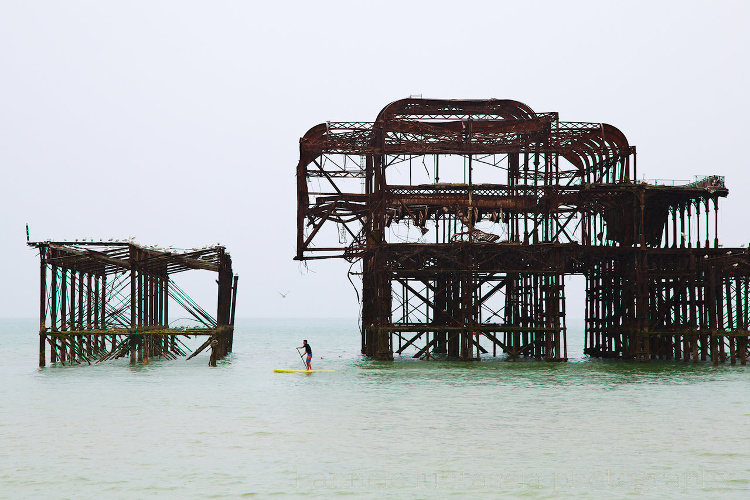How to Use Conceptual Contrast in Photography - paddle boarder with relics in the ocean