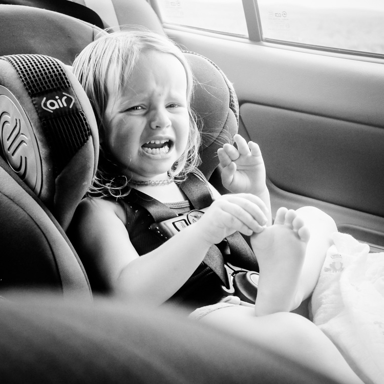 Crying girl in car. How to Photograph Your Family Vacation