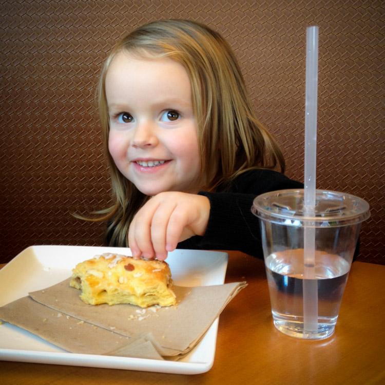 Little girl eating a snack.
