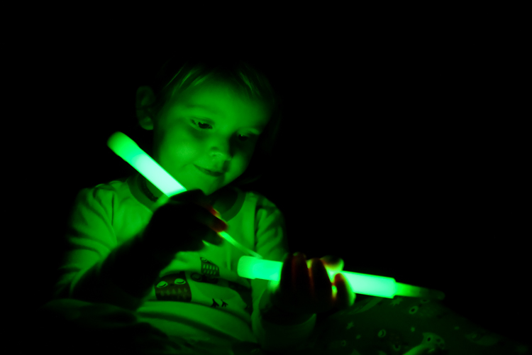 A child playing with glow sticks.